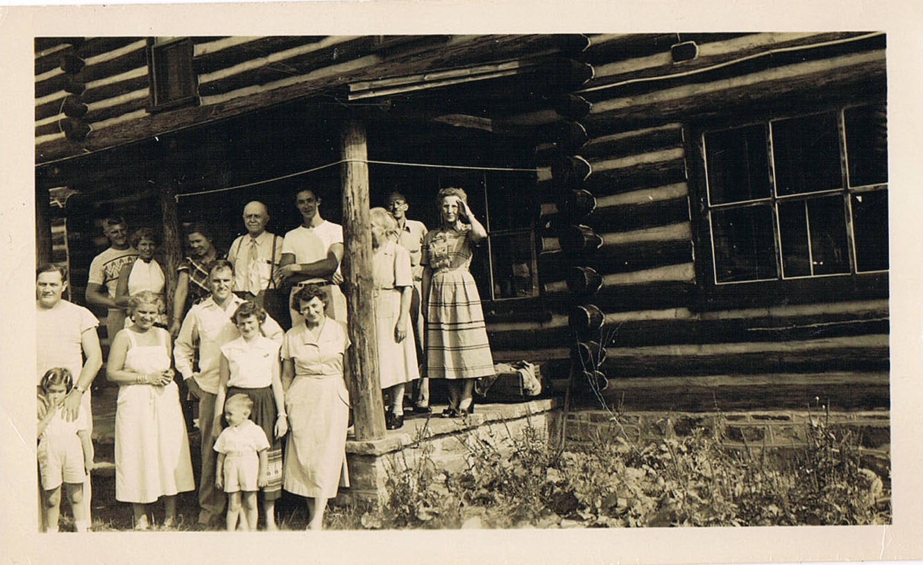 My grandfather is standing beside my mom, at the far left of the frame; my grandmother, in a dark plaid dress, is on the porch, third from the left.